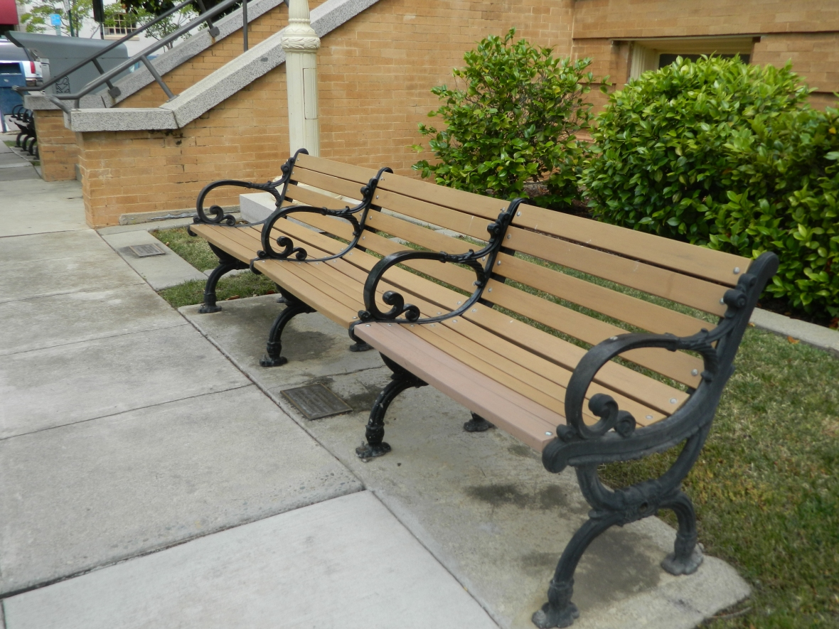Photo of empty benches lining a sidewalk