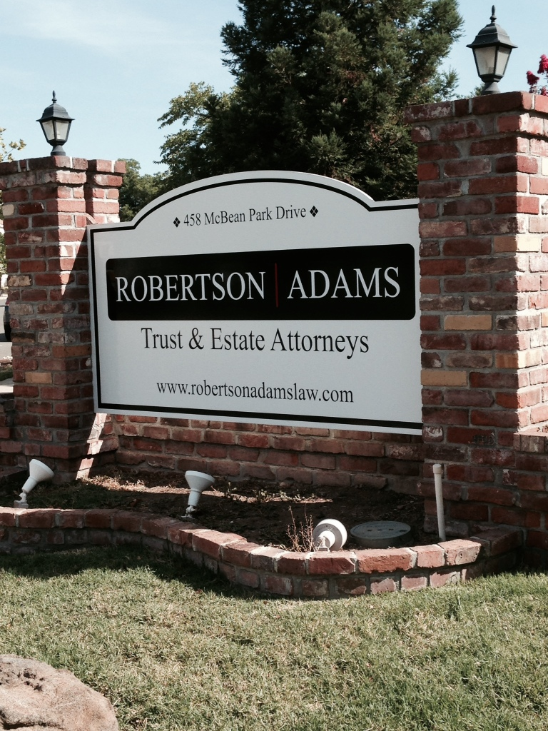 Robertson | Adams sign. Large white sign with the Robertson | Adams logo in black, placed between two brick columns.